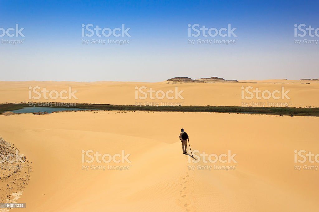 man in middle of desert heading long water source stock photo