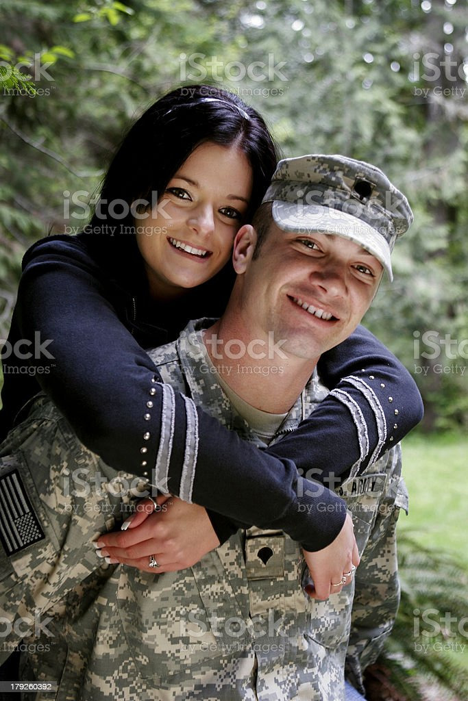 Man in military uniform being hugged by his partner royalty-free stock photo