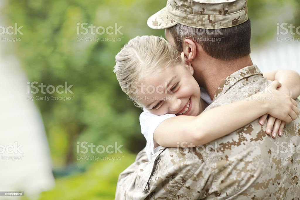 Man in military uniform carrying a little girl stock photo