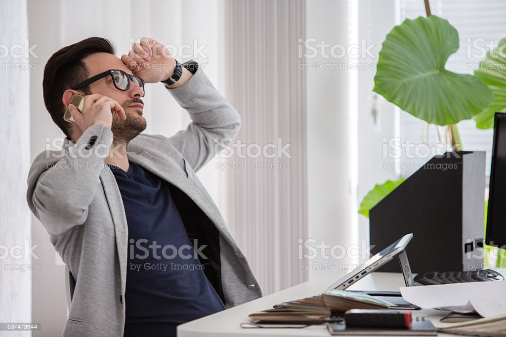 Man in modern office talking on mobile phone stock photo