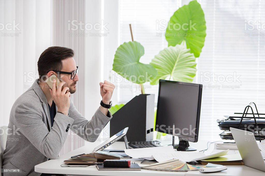 Man in modern office talking on the phone stock photo