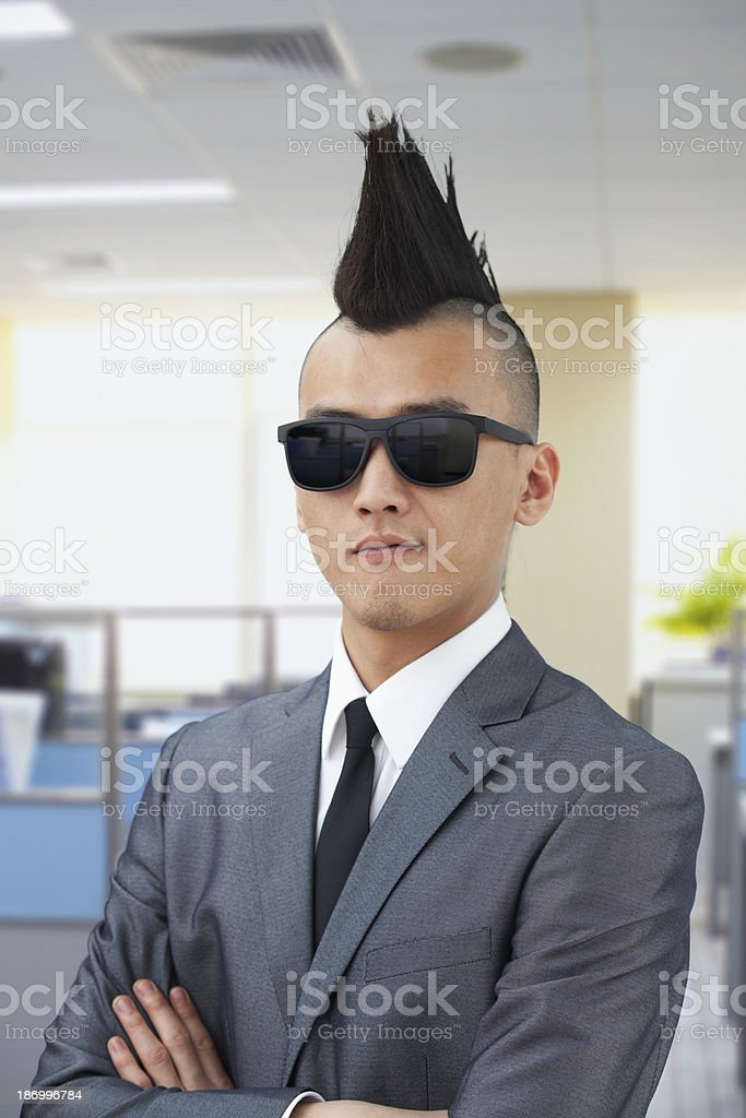 A man in mohawk wearing black sunglasses and a tie stock photo