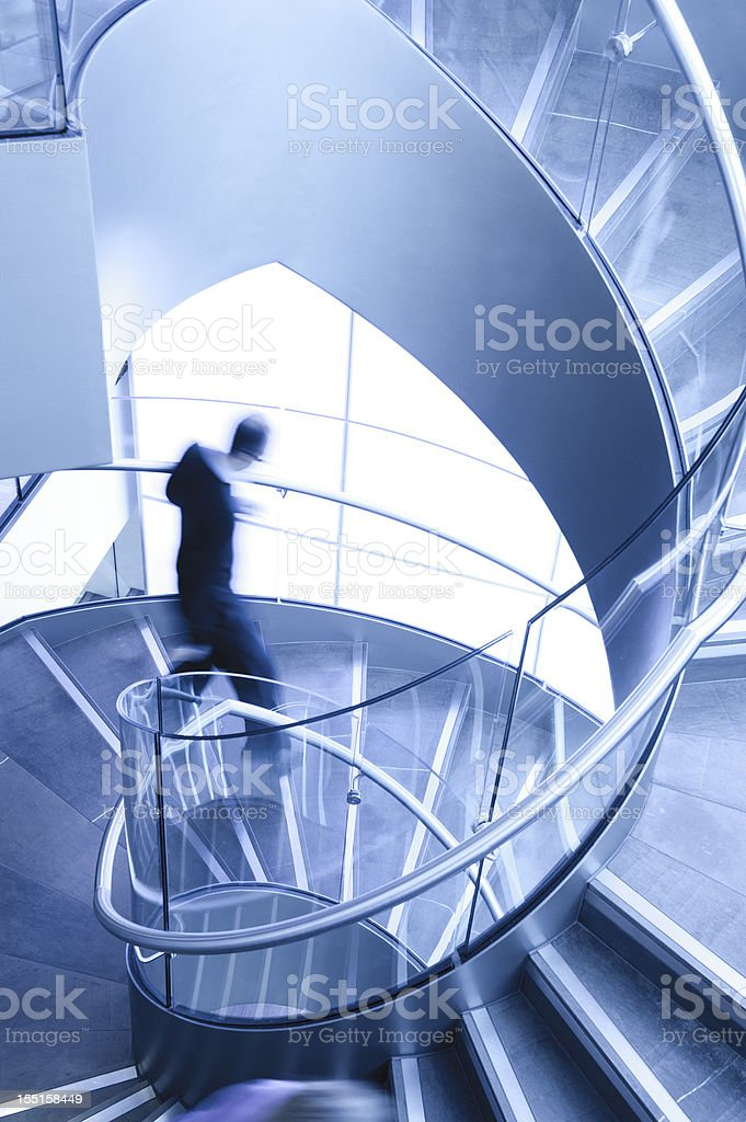 Man in Motion on Spiral Staircase stock photo