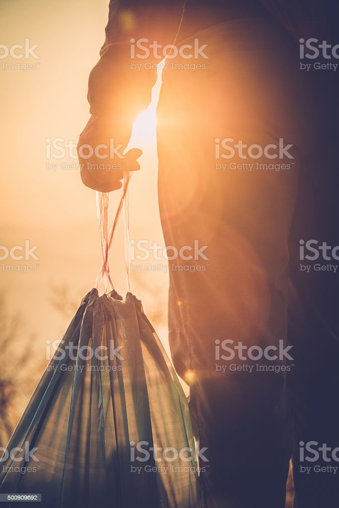 Man in Nature Holding Garbage Bag, Sunset, Close-up stock photo