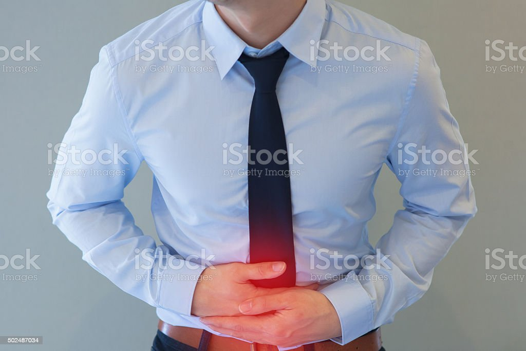 Man in office uniform having a stomachache stock photo