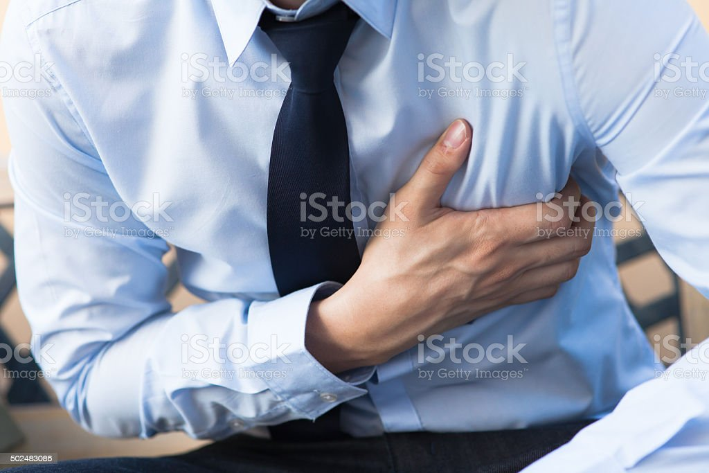 Man in office uniform having heart attack / heart burn stock photo