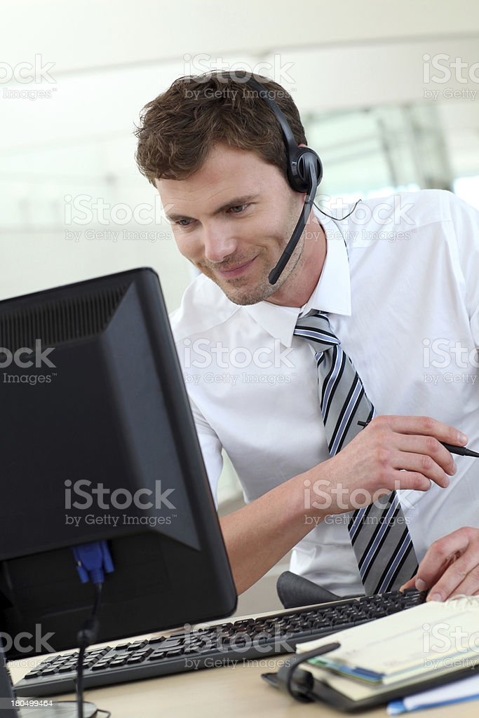 Man in office working with headphone and computer royalty-free stock photo