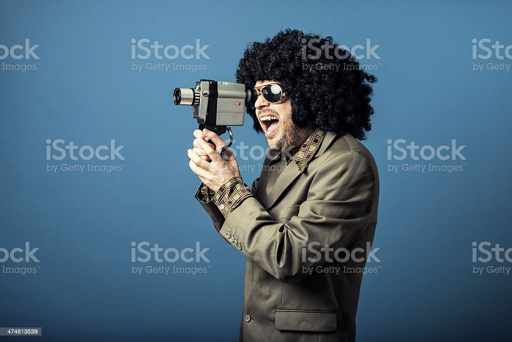 Man in old suit shoots a video with retro camera royalty-free stock photo