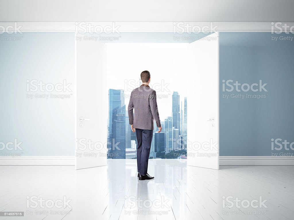 Man in opened doors looking at city stock photo