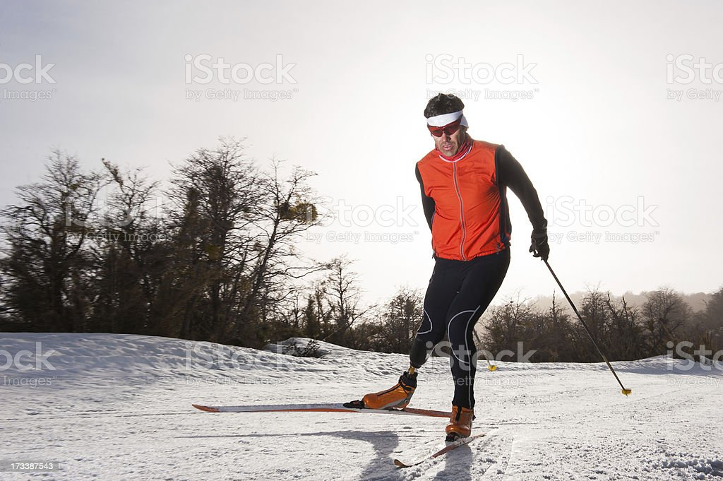 Man in orange cross country skiing stock photo