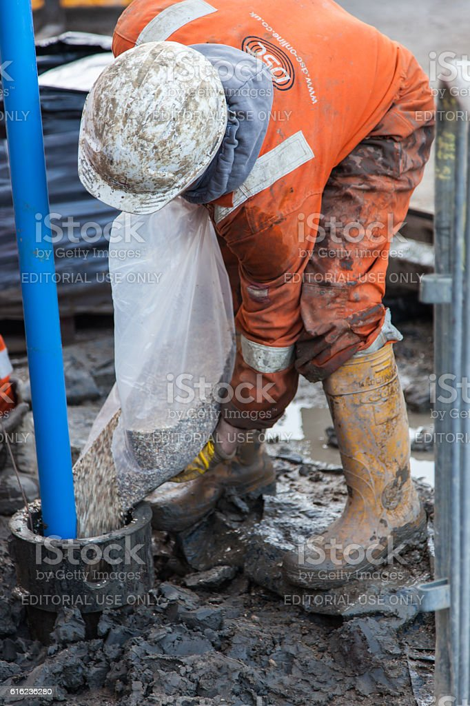 Man in orange overalls work on a borehole stock photo