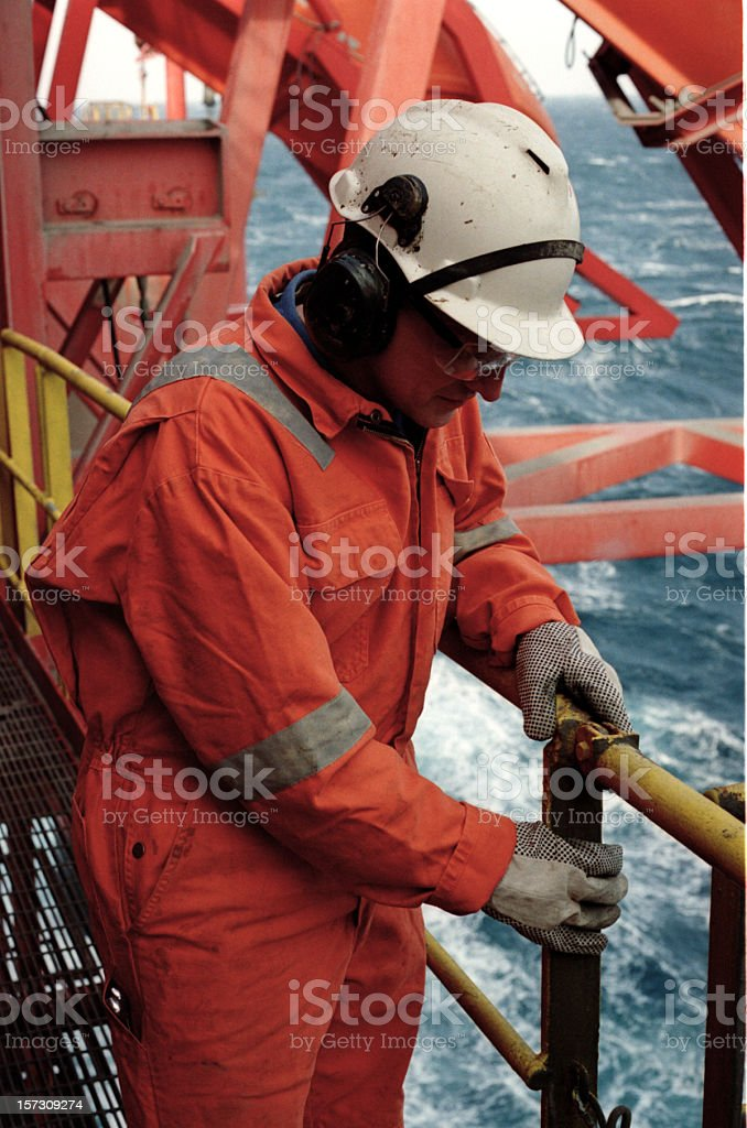 Man in orange uniform and white helmet working on an oil rig royalty-free stock photo