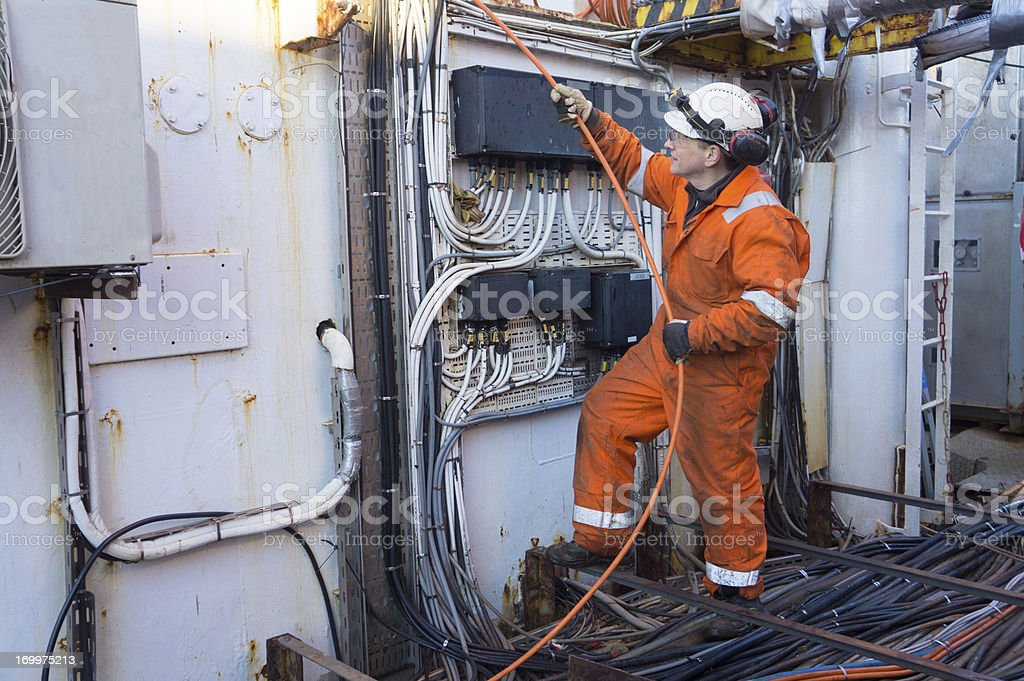 Man in orange work clothing holding a thin orange cable royalty-free stock photo