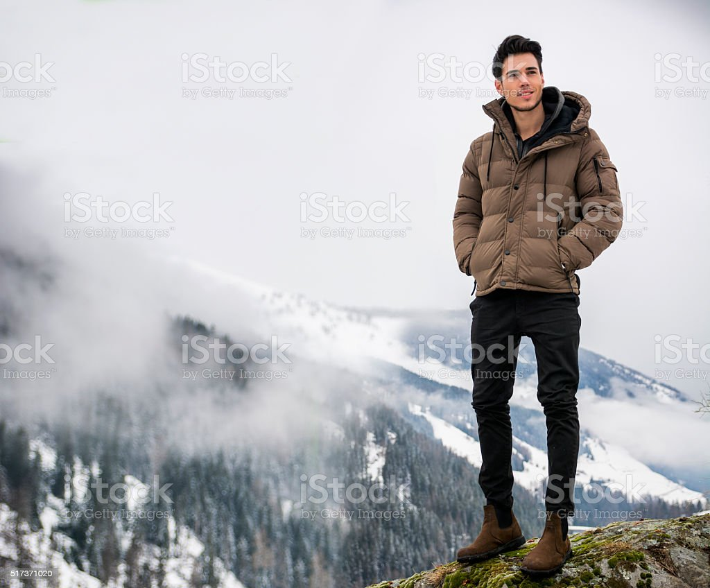 Man in outerwear sitting while looking at camera stock photo