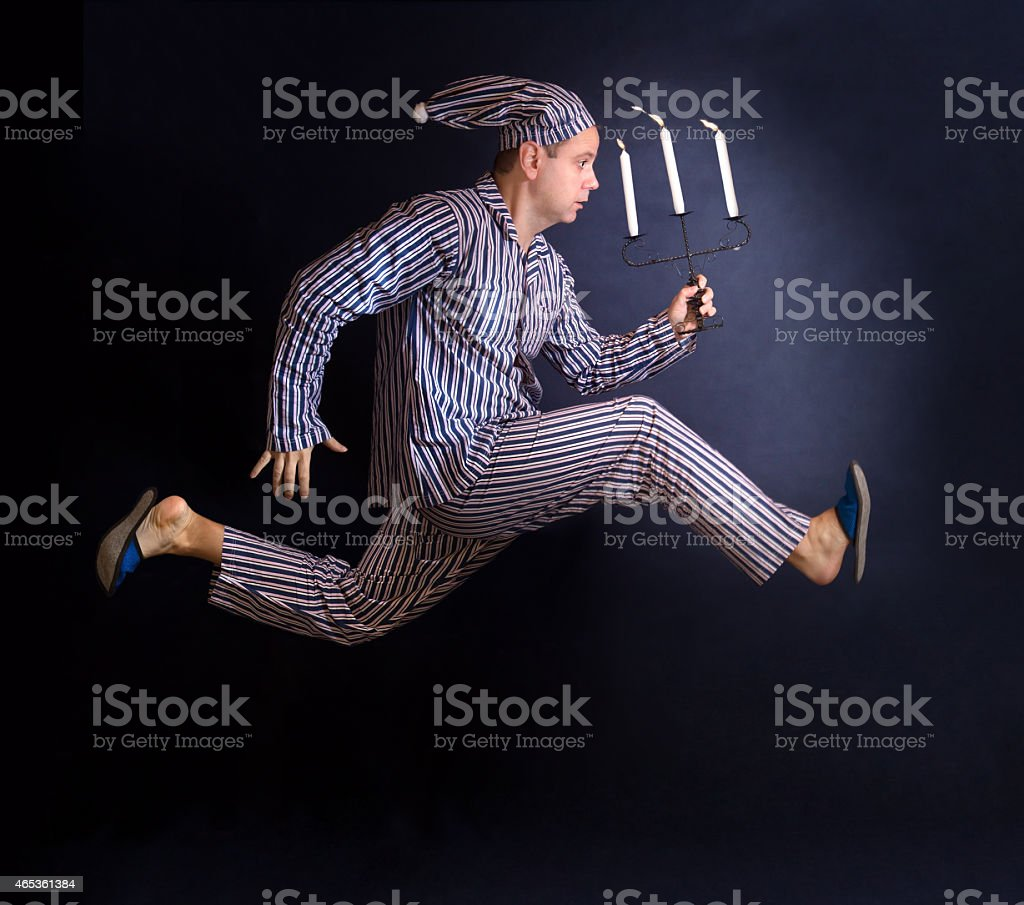 man in pajamas running with a candlestick stock photo