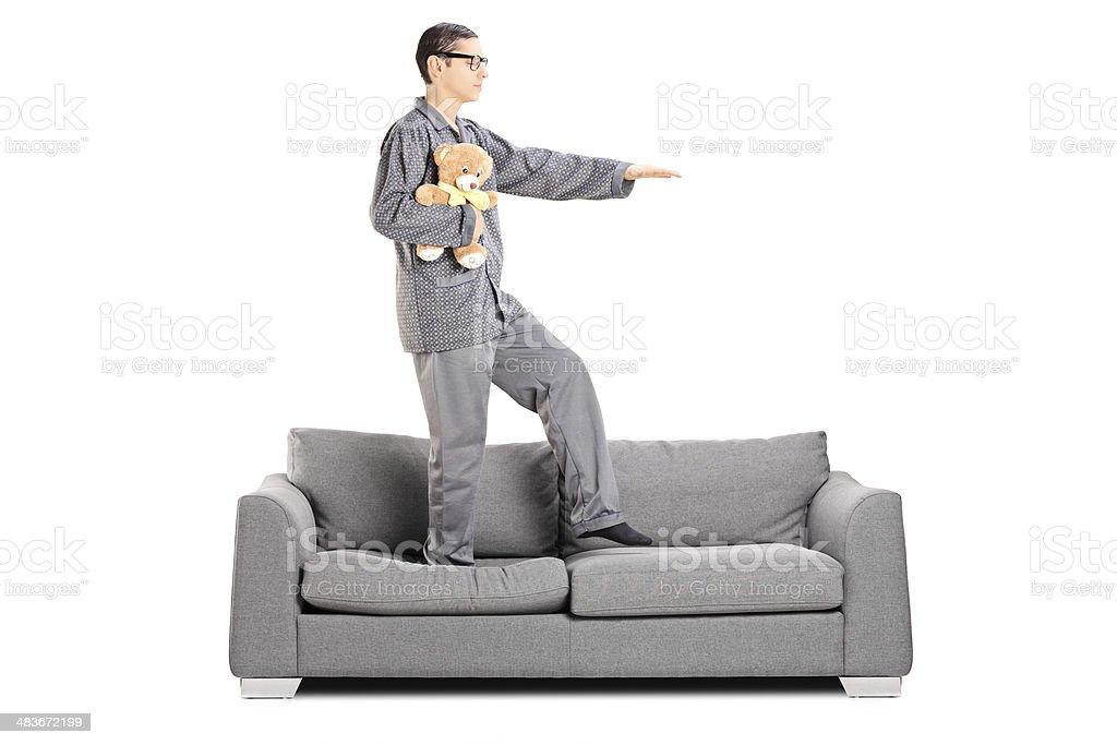 Man in pajamas sleepwalking on sofa stock photo