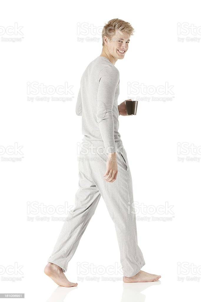 Man in pajamas walking with a cup of coffee royalty-free stock photo