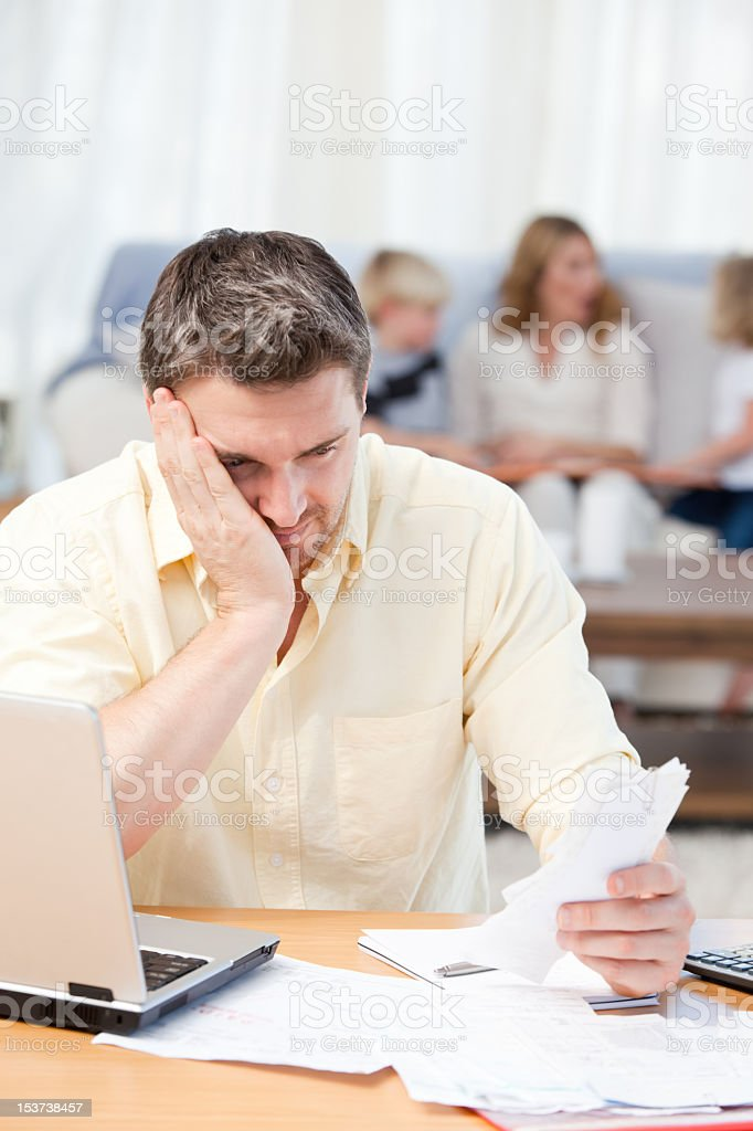 Man in pale yellow button up calculating his bills royalty-free stock photo