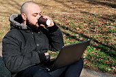 Man in park doing business on laptop and drinking coffee