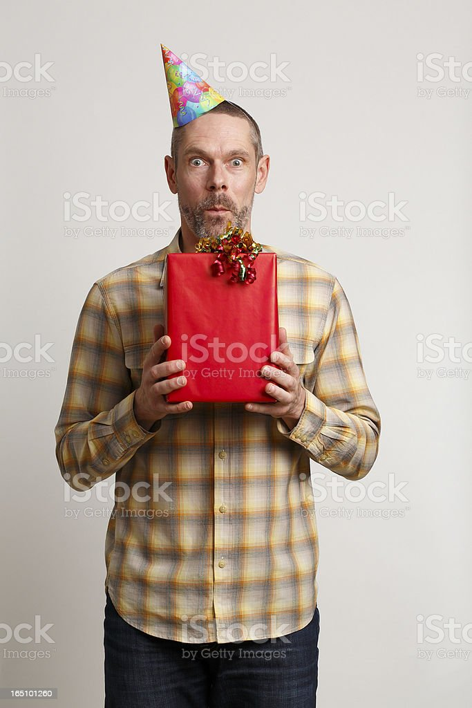 Man in Party Hat Holding Gift And Showing Surprise royalty-free stock photo