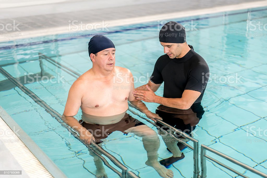 Man in physical therapy in the water stock photo