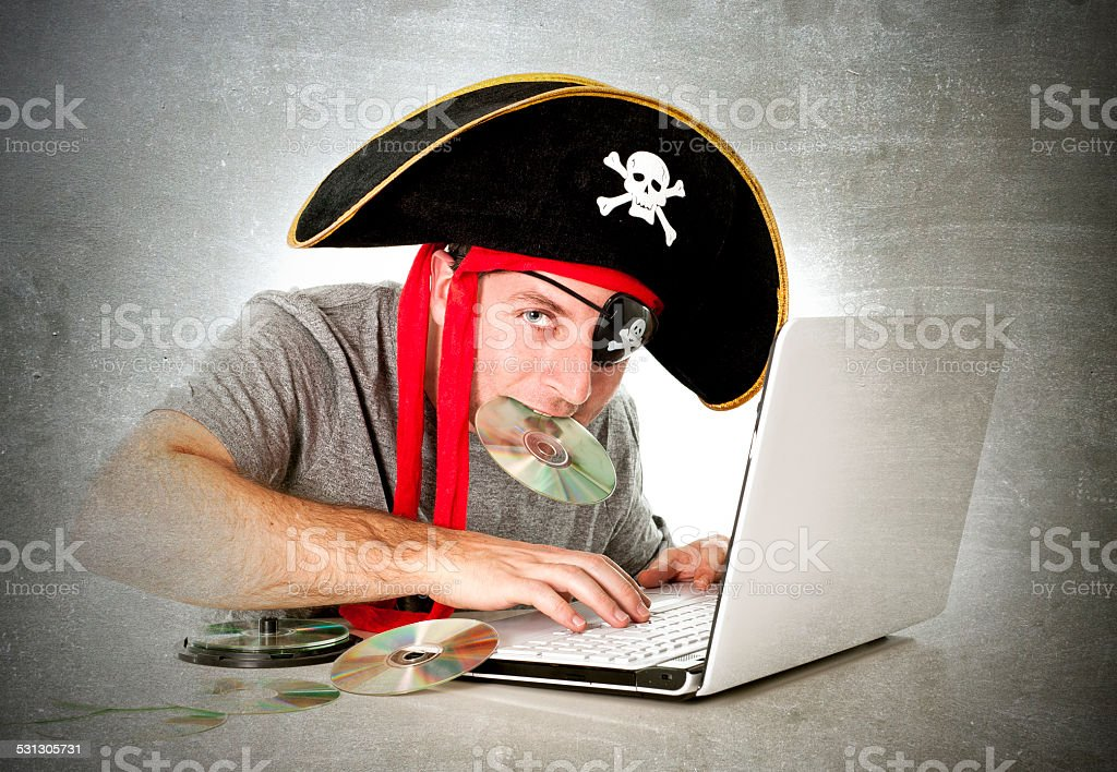 man in pirate hat downloading music and movies computer files stock photo