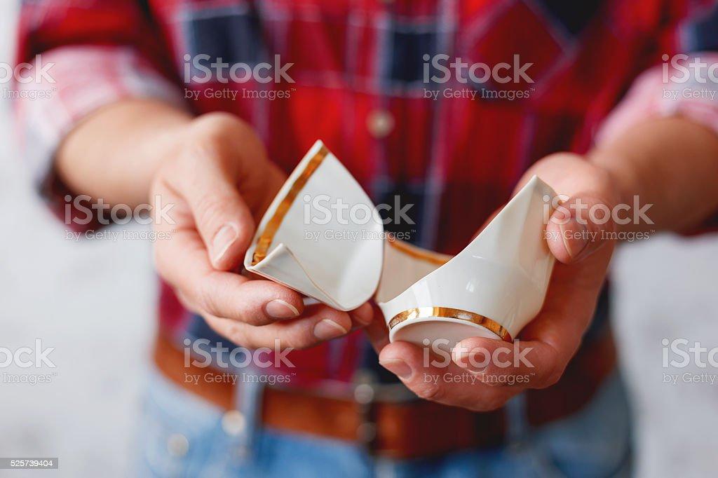 Man in plaid tartan shirt holds a broken white cup. stock photo