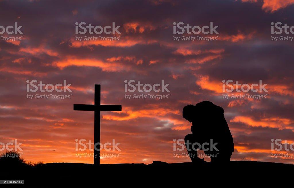 Man In Pray Cross stock photo