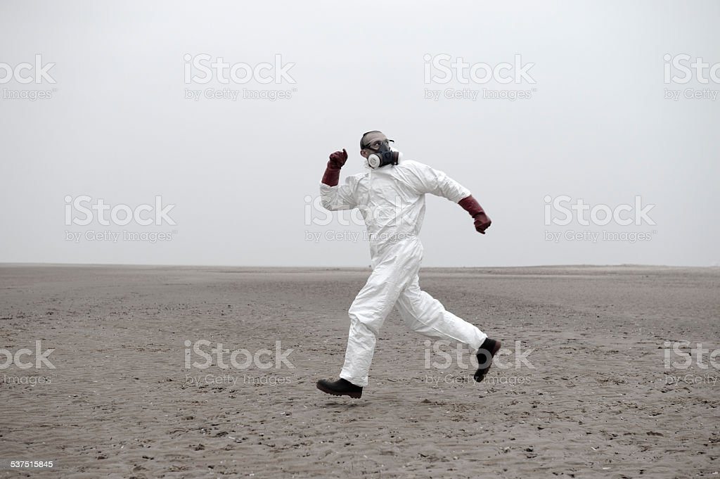 Man in protection suit running away stock photo