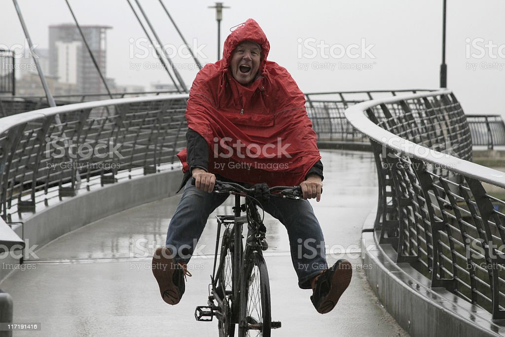 Man in rain on bike having fun stock photo