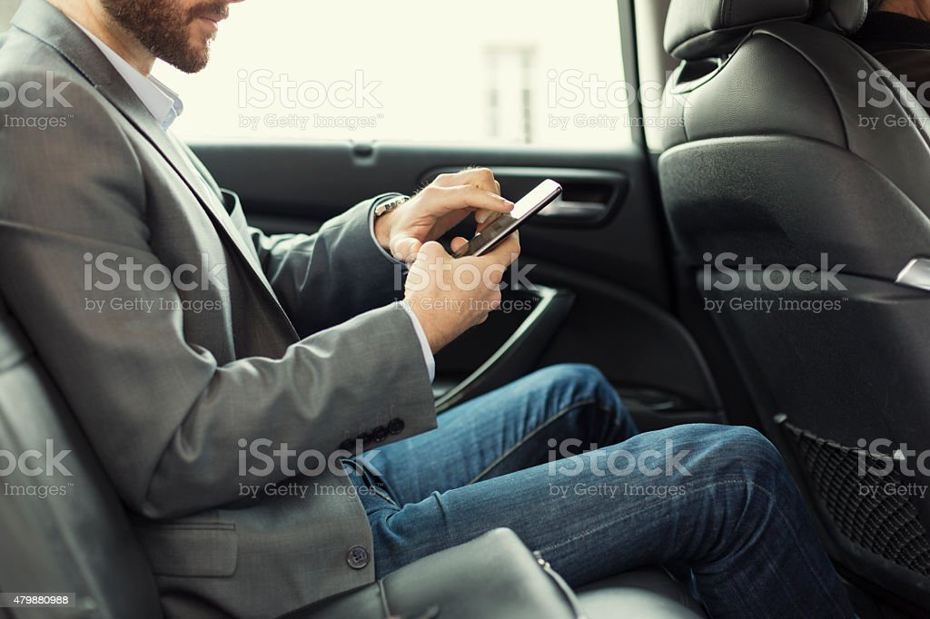 Man in rear of the car typing on mobile phone stock photo