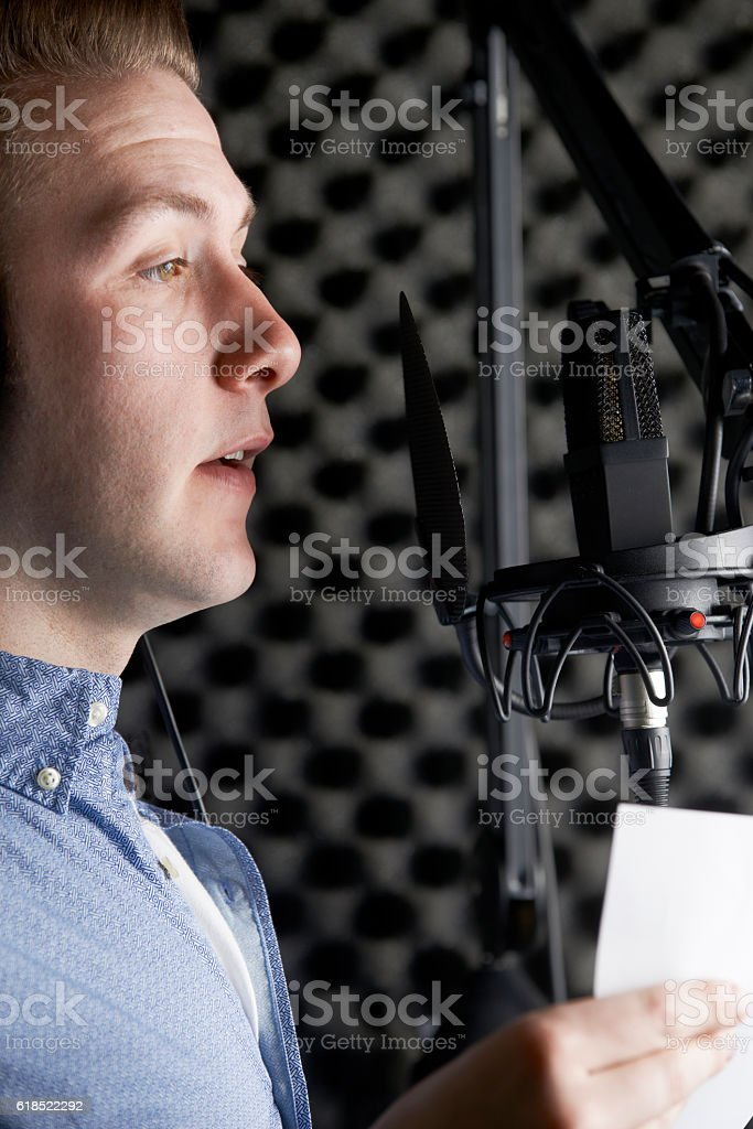 Man In Recording Studio Talking Into Microphone stock photo