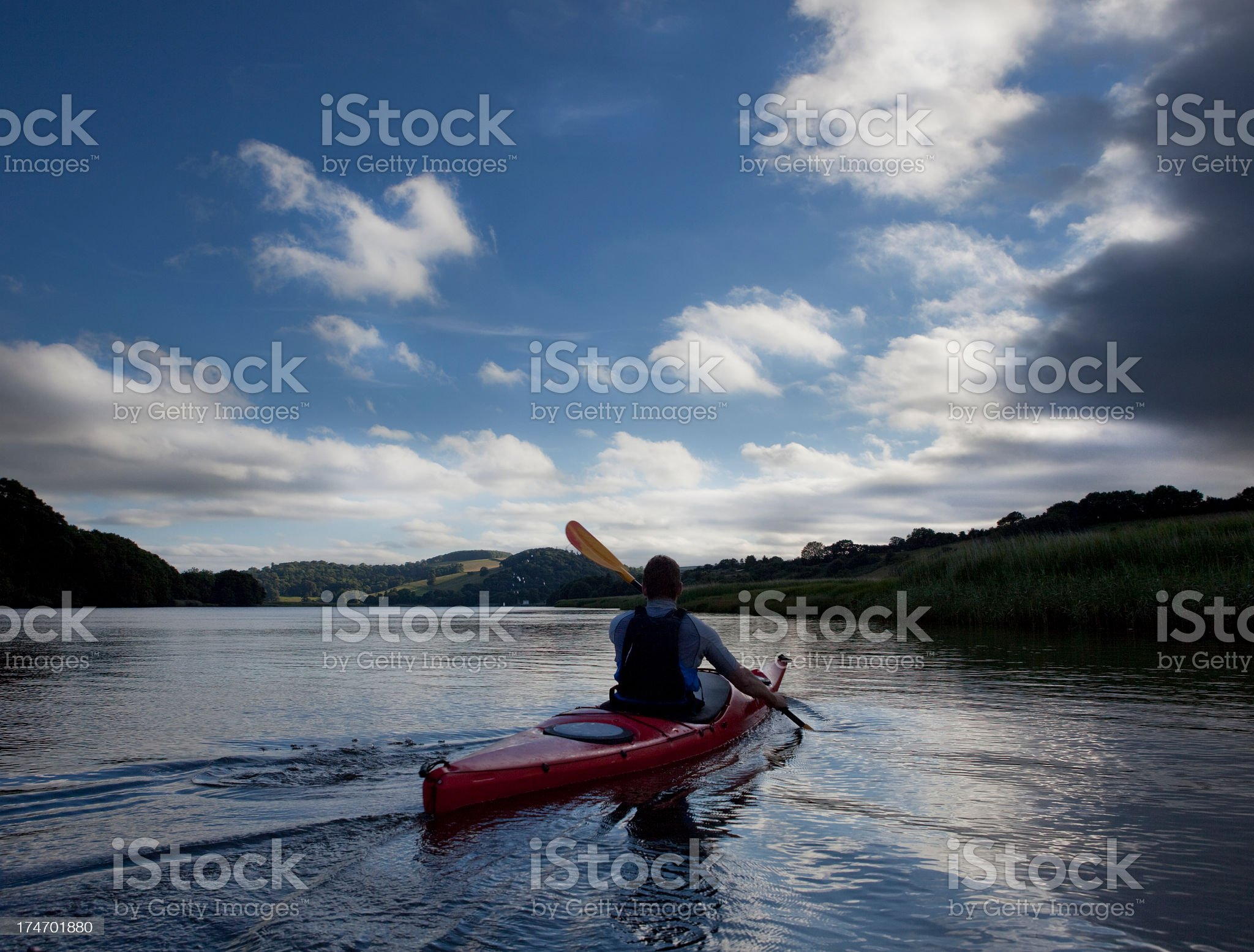 Man in red kayak paddling on a calm lake on a sunny day royalty-free stock photo