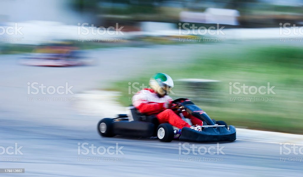 Man in red racing a go kart on a track stock photo