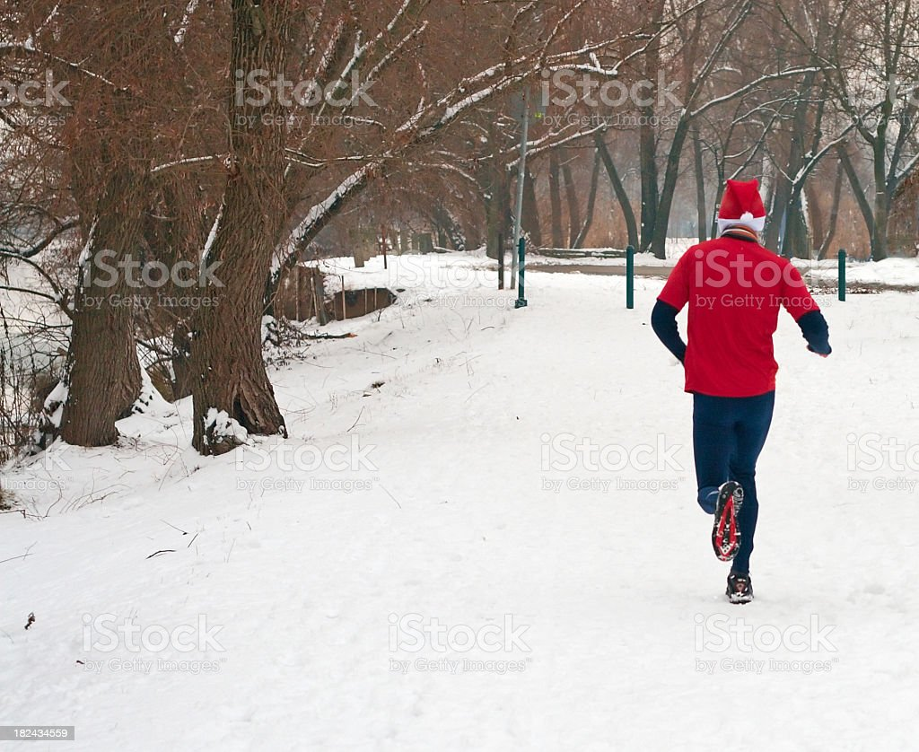 Man in red running in the snow stock photo