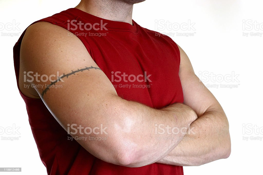 Man in red shirt with arms crossed and tattoo stock photo