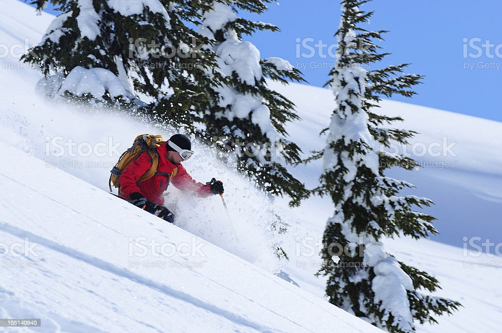 Man in red skiing down snowy mountain stock photo
