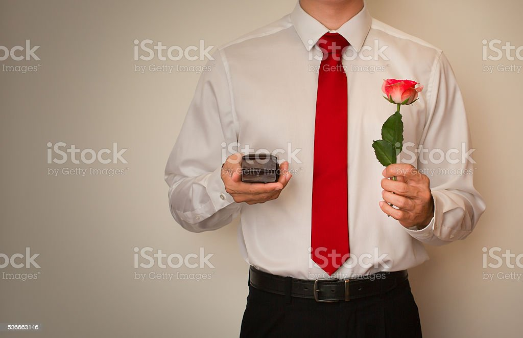 Man in red tie, holding a ring box and rose stock photo