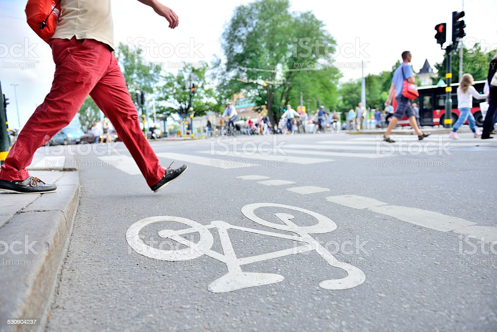 Man in red trousers crossing street with traffic stock photo