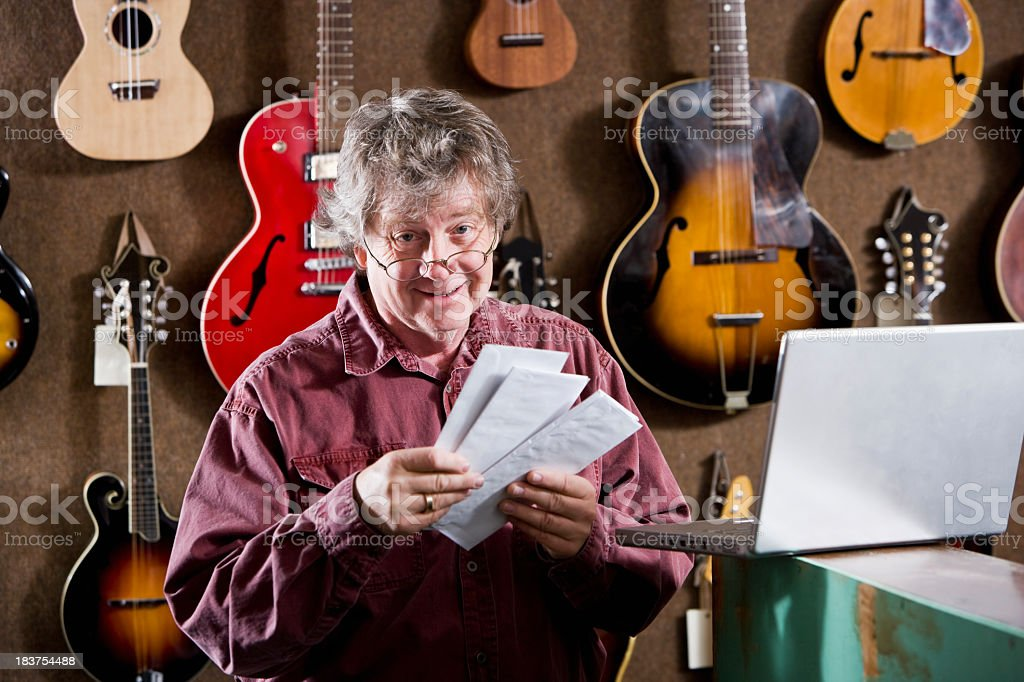 Man in retail store selling acoustic guitars royalty-free stock photo