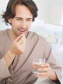 Man in robe holding vitamin pill