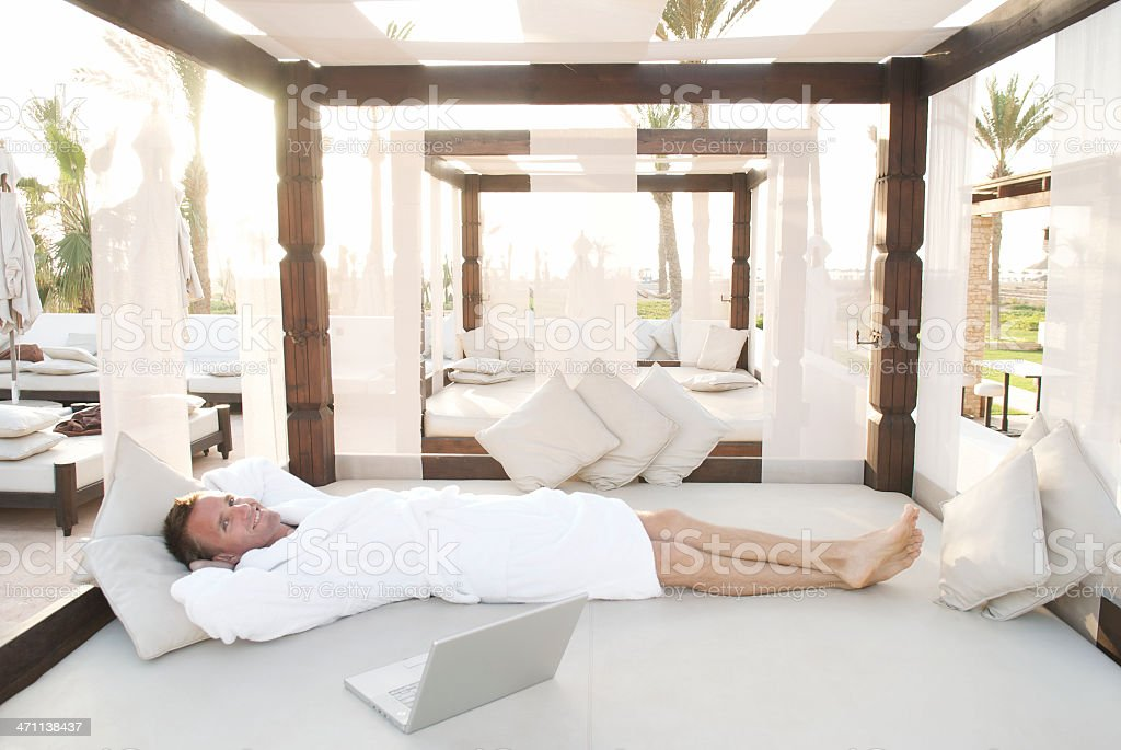 Man in Robe Reclines on Outdoor Canopy stock photo