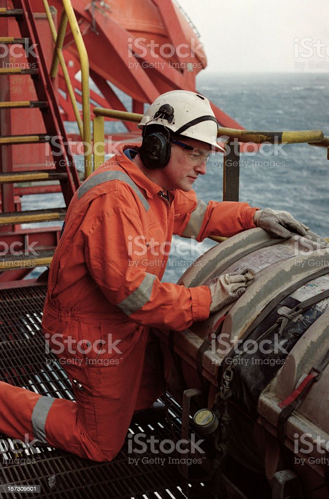 A man in safety gear working on a oil rig stock photo