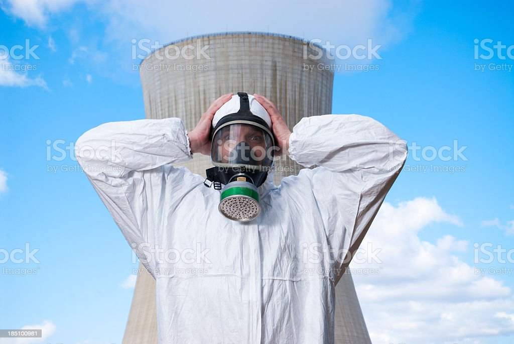 Man in safety suit standing in front of nuclear power plant royalty-free stock photo