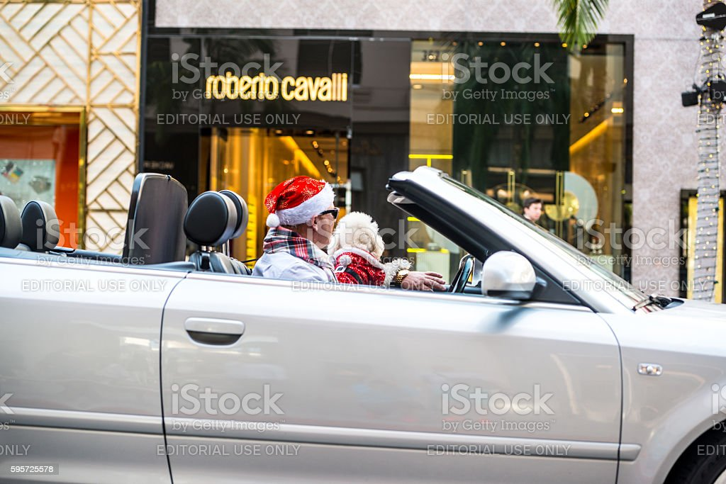 Man in Santa Hat driving Audi Cabriolet on Rodeo Drive stock photo