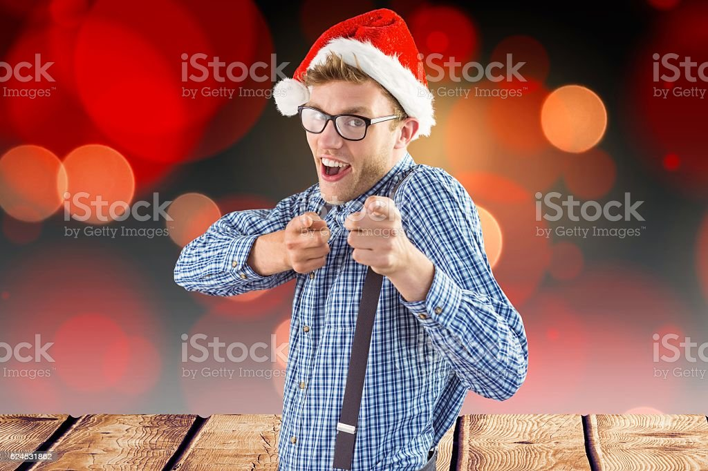 Man in santa hat gesturing against digitally generated background stock photo