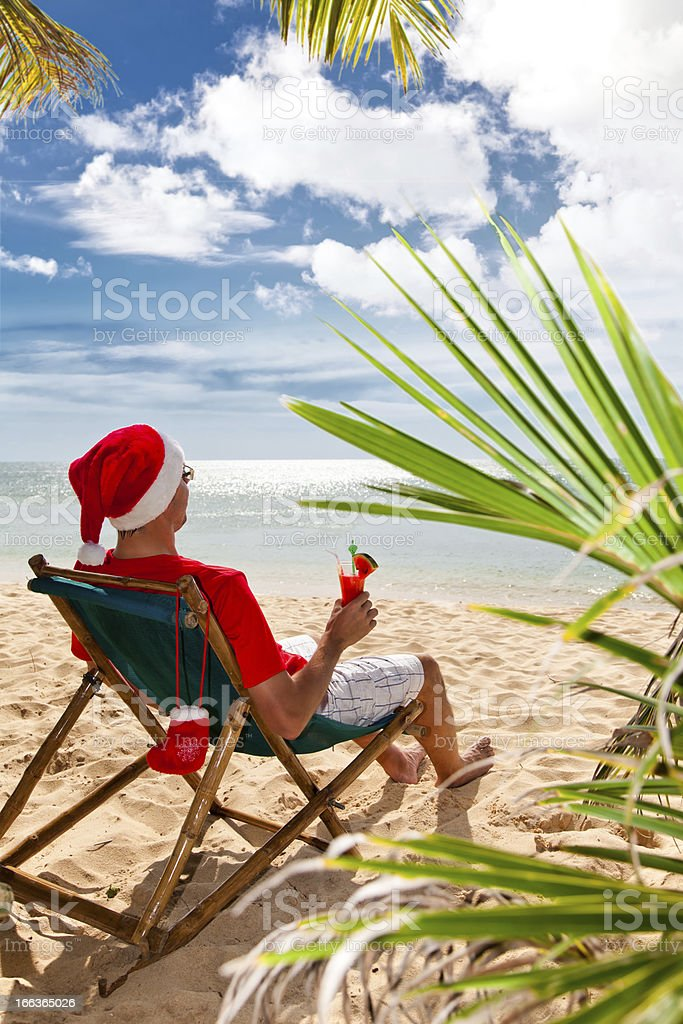 Man in Santa's hat with cocktail sitting on the beach royalty-free stock photo