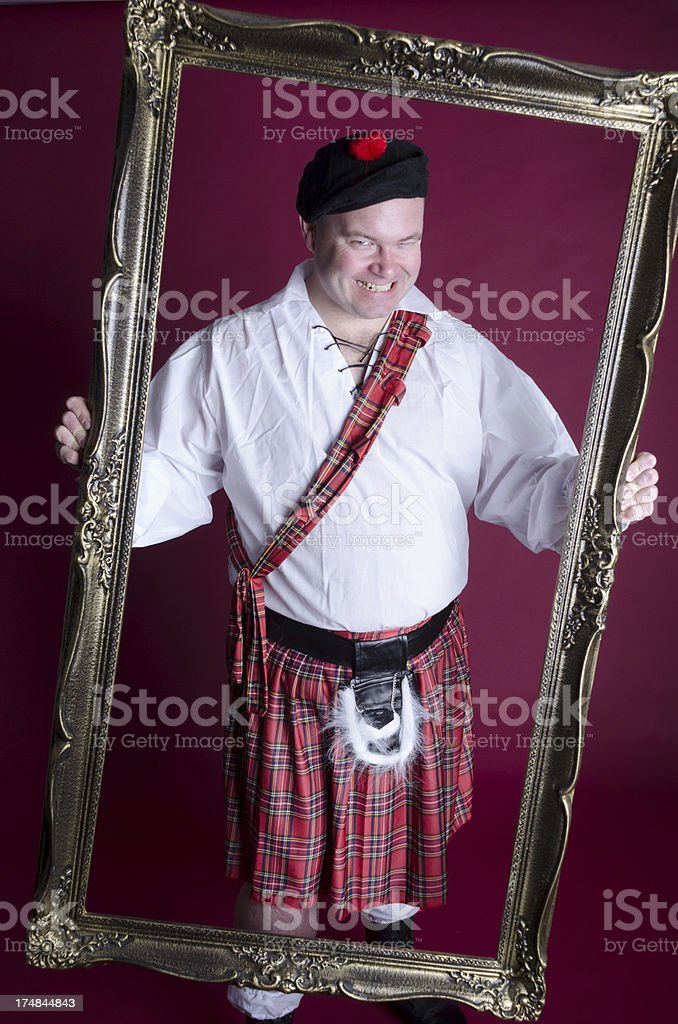Man in Scottish outfit grinning evilly through frame. royalty-free stock photo