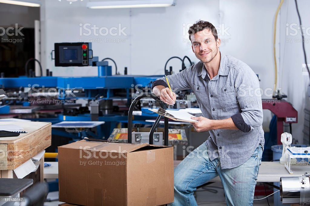 Man in screen printing factory stock photo