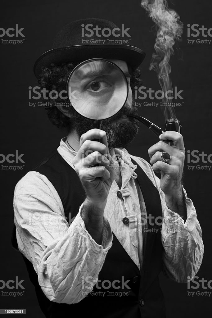 Man in Sherlock Holmes costume holding magnifier glass stock photo